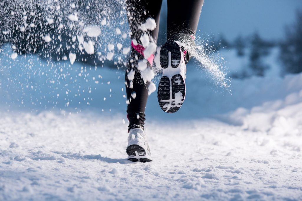 Woman's feet running in cold winter snow