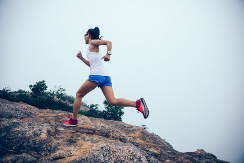 athletic woman running up mountain