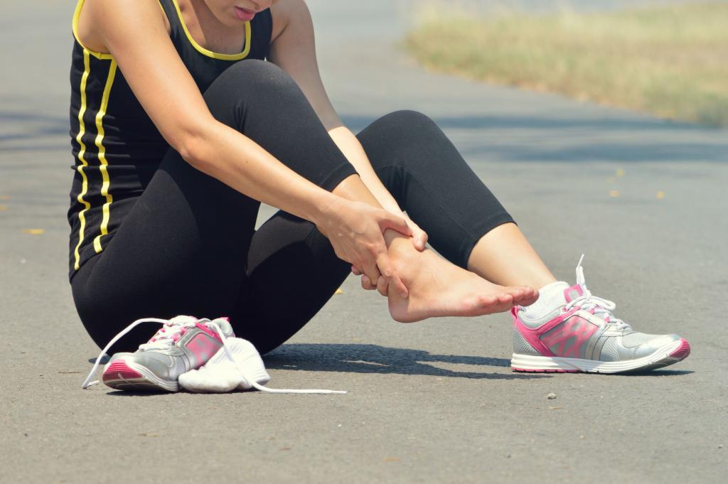 young woman suffering from an ankle injury while exercising and running