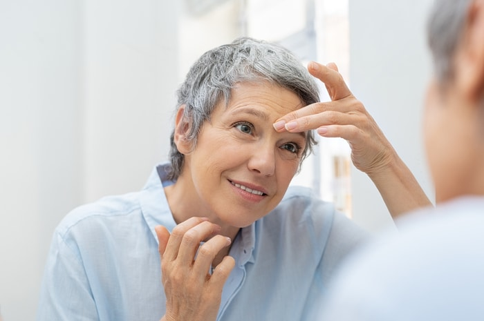 woman checking wrinkles on face