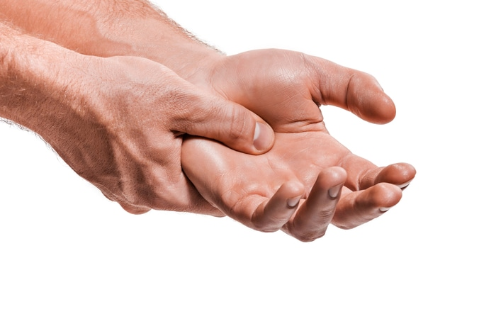 man massaging hand with arthritis pain
