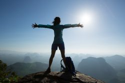 woman hiker happy on top of mountain
