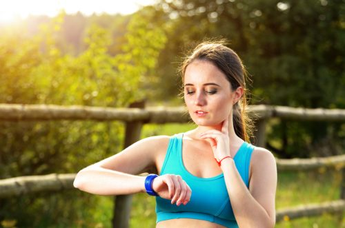 Woman using fitness bracelet to check heart rate after cardio workout