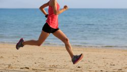 young fitness woman morning exercise running at beach