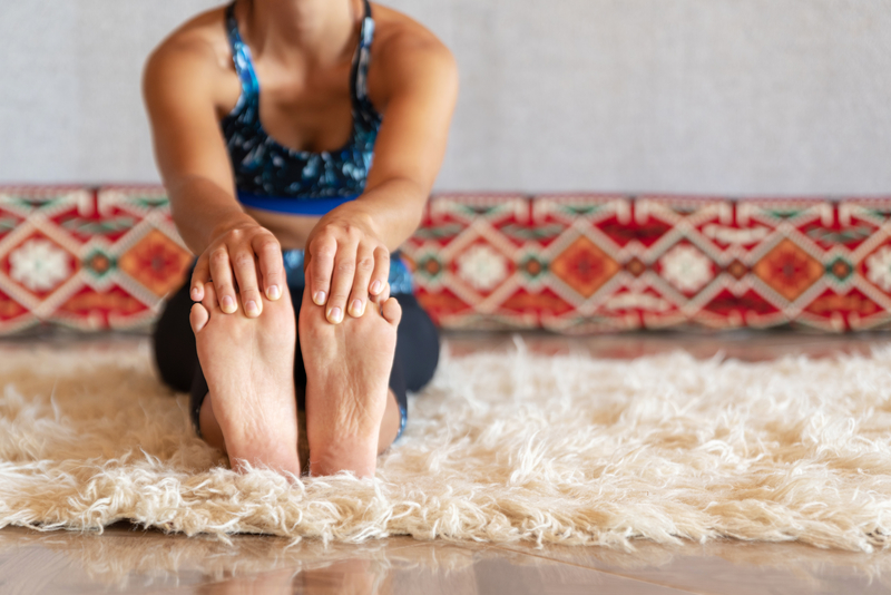Woman doing physical exercise and stretching legs, feet close up