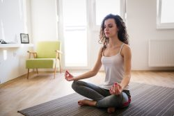 young woman in calming and relaxing meditation pose