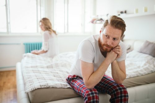 unhappy couple sitting on bed