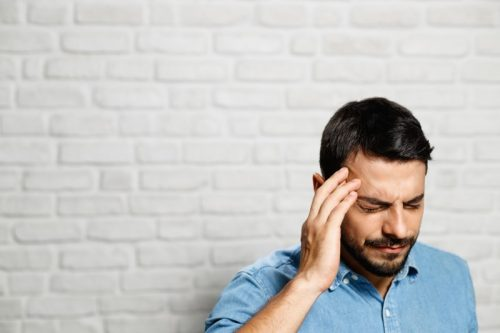 man rubbing head from anxiety headache