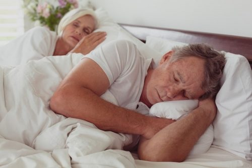 senior couple sleeping on bed