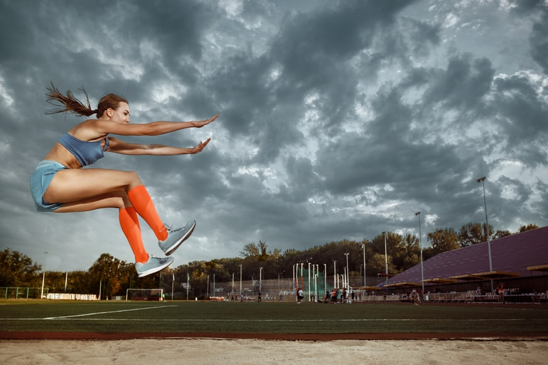 female athlete performing long jump after nitric boosting preworkout