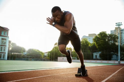 young black athlete running on racetrack